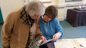 Ida Congdon (left) studying documents relating to the YMBC